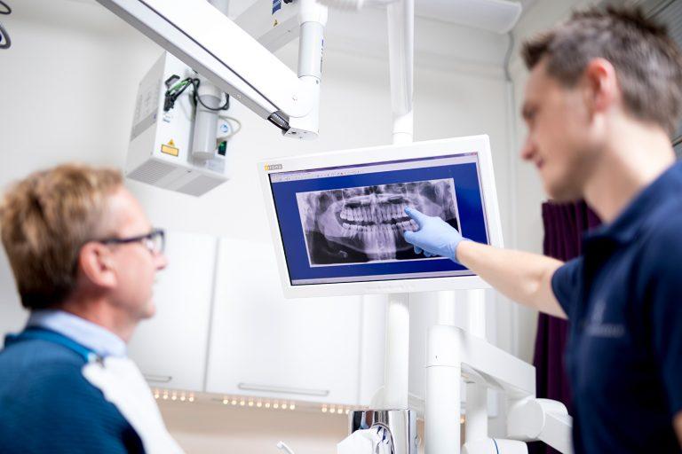 Tannlege Bjelland Viser en pasient røngten bilde
